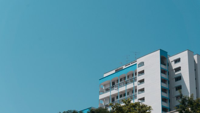 White concrete HDB building under a blue sky in the daytime
