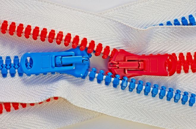 Detail of two intertwined zippers, with blue and red teeth, like male and female, on white background