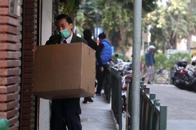 Man in black jacket carrying brown cardboard box