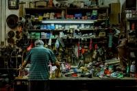 Elderly man facing a shelf of tools
