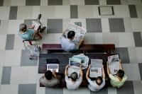 Elderly men reading newspapers