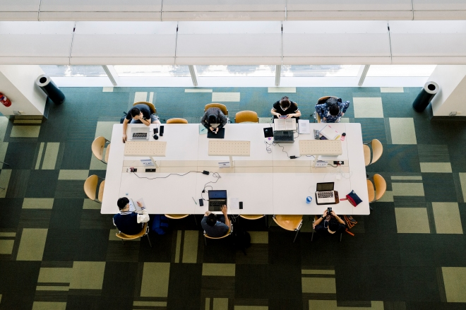Patrons at the National Library Board, seated and working around a table