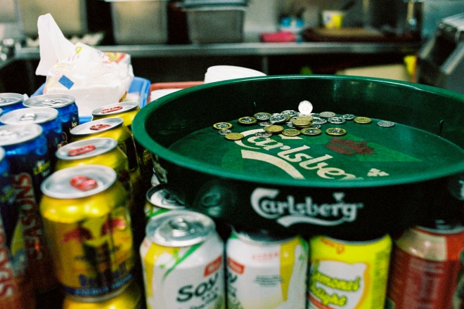 Green serving tray on a selection of canned beverages