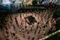 Group of dancers in circles around a stage (Photo by Ng Shi Wen)