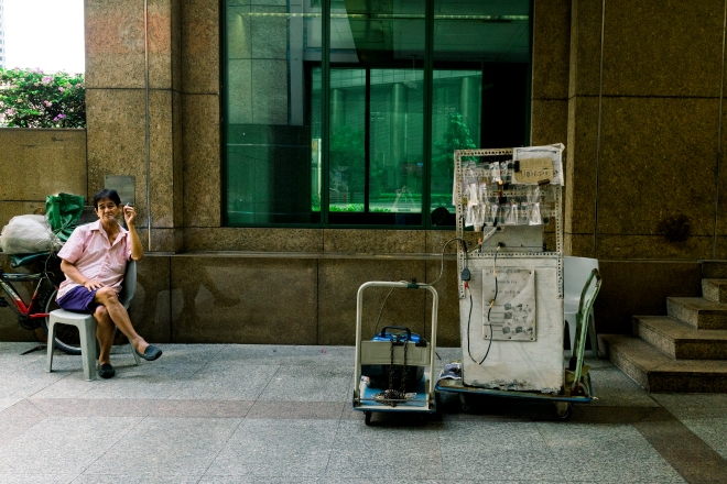 Man smoking while sitting on one side, with a pushcart of hardware equipment on the other side of the photo (Photo by Ng Shi Wen)