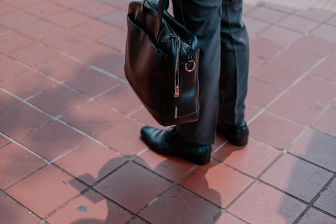 Businessman with black bag (Photo by bady abbas on Unsplash)